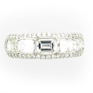 A white metal ring with rectangular stones and smaller Stones and on either side