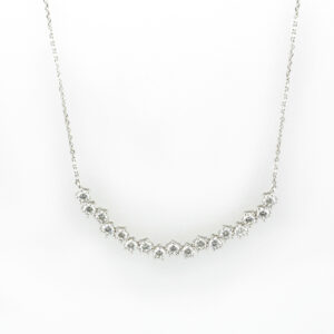 14 karat white gold necklace has a curved row of 1.36 carats of diamonds that are FG/VS rated.