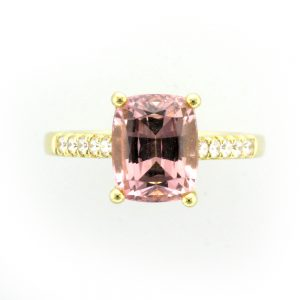 Yellow gold ring with large rectangular pink stone and white stones in the band