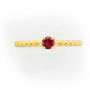 This 14 karat yellow gold stacking ring has a pink tourmaline.