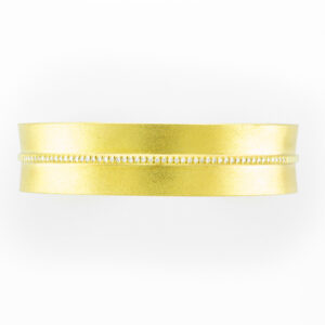 14 karat yellow gold cuff bracelet has stone finish and a line of 0.25 carats of diamonds through the center.