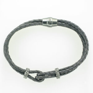 four strand braided black and brown bracelet has a magnetic clasp and stations that are black rhodium.