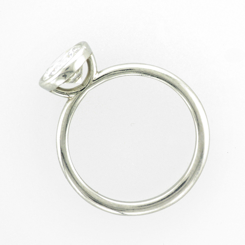 Platinum ring has a bezel solitaire.