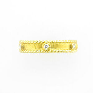 This 14 karat stacking band has a melee rope edge and bezel set stones with a total weight of 0.12 carats.