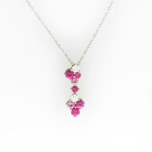 This 18 karat white gold pendant has two diamonds with a total weight of 0.12 carats, three rubies with a total weight of 0.28 carats, and four pink sapphires with a total weight of 0.33 carats.