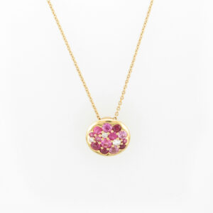 This 18 karat rose gold tango pendant has three rubies with a total weight of 0.21 carats, 10 pink sapphires the total weight of 1.0 carats, and three diamonds with a total weight of 0.21 carats.