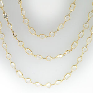 This 18 karat yellow gold necklace is 34 inches long and has multi shape white topaz with a total weight of 45.43 carats.