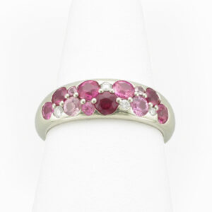 This 18 karat while gold ring has three rubies with a total weight of 0.49 carats, nine pink sapphires with a total weight of 1 carat, and diamonds with a total weight of 0.09 carats.